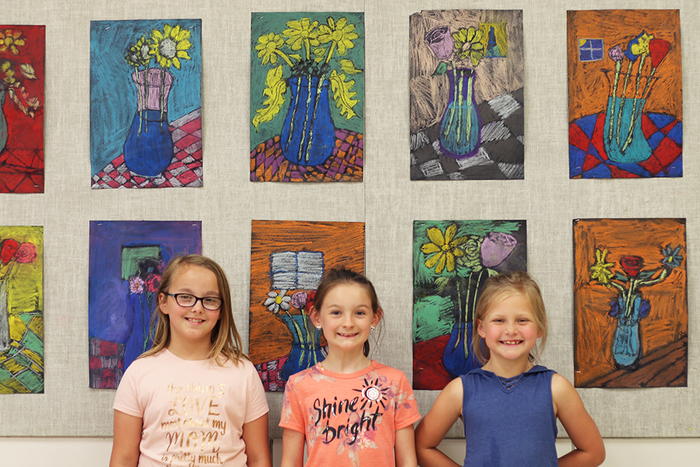Students pose in front of artwork.